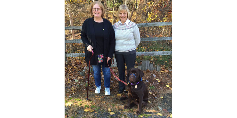 ADAI  volunteer Karen Bade (right) and Cedar help Liz Morrison achieve independence.