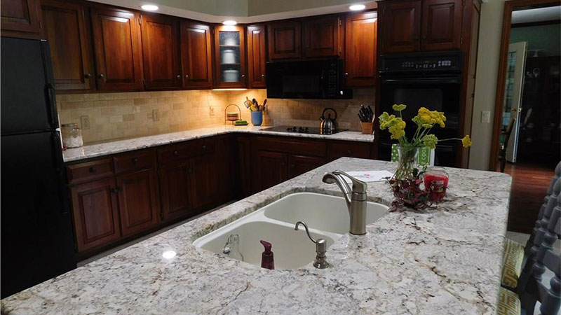Granite countertops and tumbled stone backsplash.