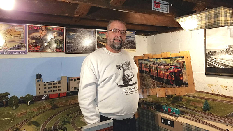 Gary Cornell poses with one of his train photos, surrounded by a carefully constructed model train layout.