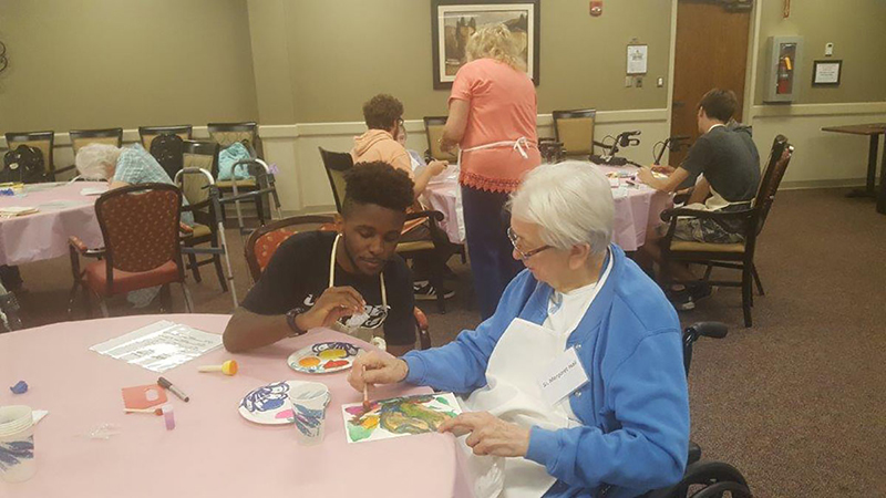 Sr. Margaret Hall works with LU student Aaron Brown creating a masterpiece!